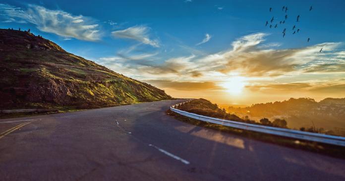 Straßenkurve mit Sonnenuntergang im Hintergrund
