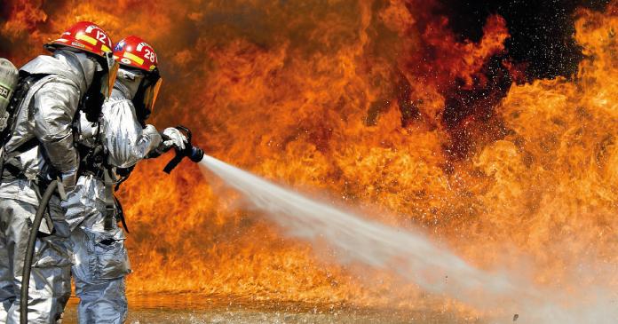 zwei Feuerwehrmännern in Schutzanzügen beim Löschen einer Feuerwand