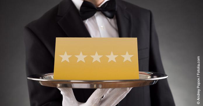 Butler serviert auf einem silbernen runden Tablett eine goldene Karte mit fünf silbernen Sternen